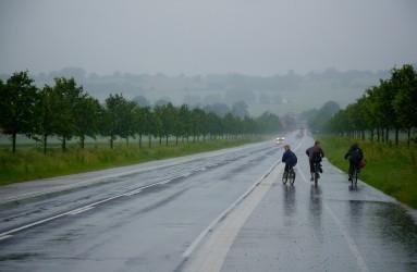 Drenge cykler på Adlers Alle i regnvejr